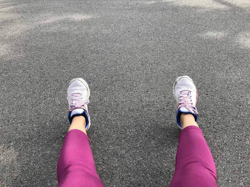 Woman leg wear pink pant and sneaker shoe on concrete road royalty free stock photography