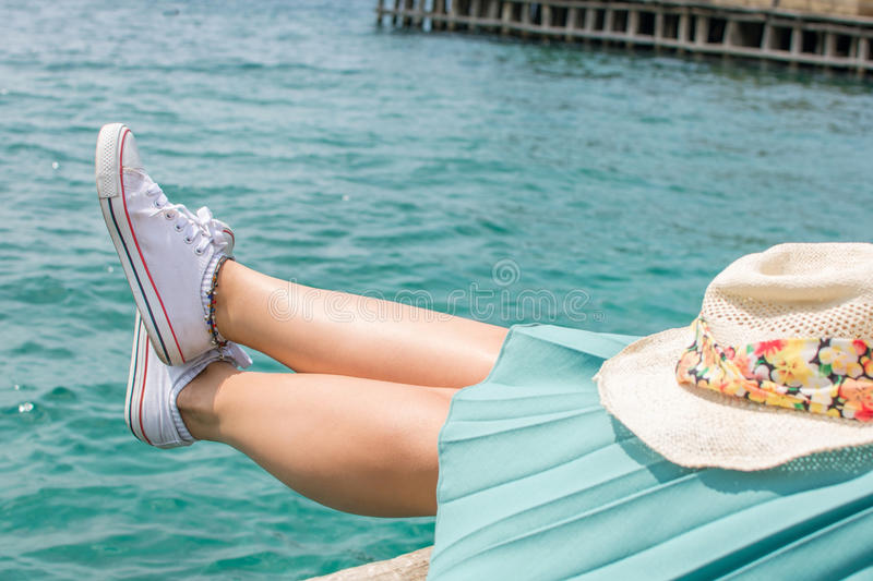 Woman legs above water on a dock royalty free stock photography