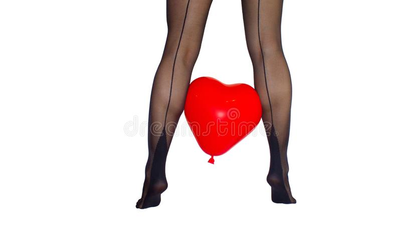 Woman legs from the back in black tights with red heart baloon between on white background stock image