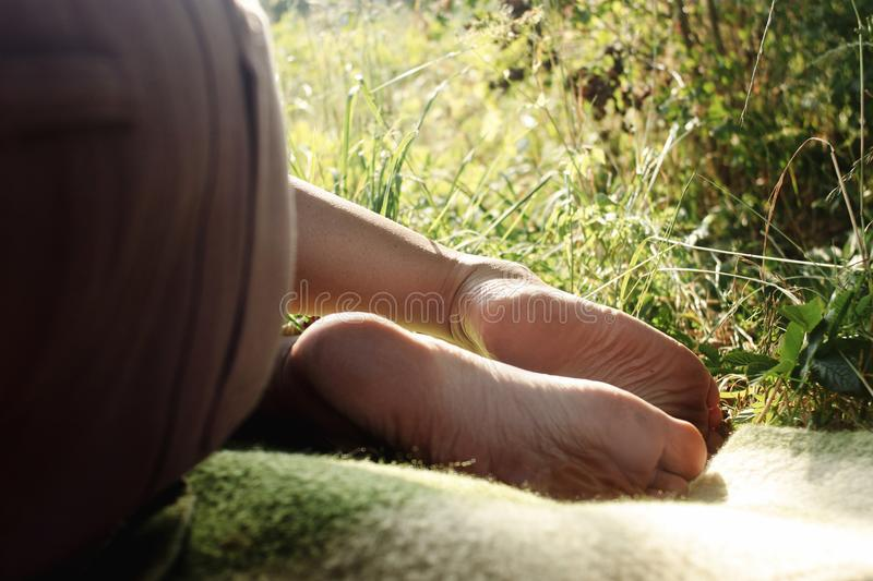 Woman legs barefoot on blanket on a picnic in a garden under war royalty free stock images