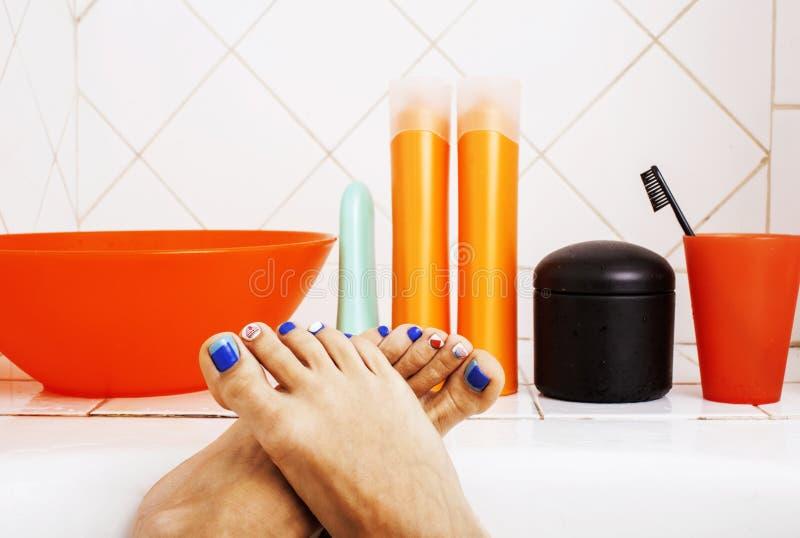 Woman legs in bathroom with lot of stylish stuff for care, pedicure creative design, hygiene spa mani pedi concept stock image
