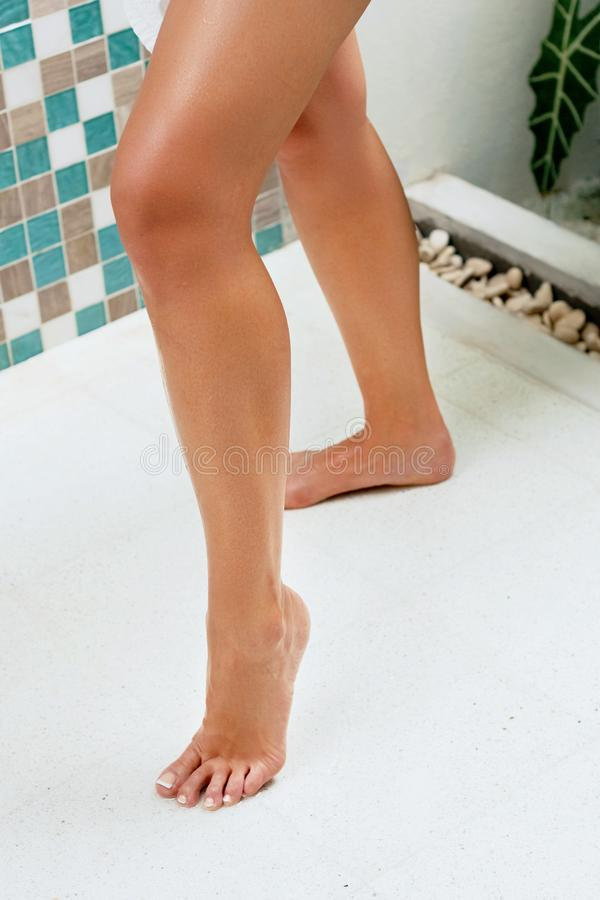 Woman legs in bathroom with smooth soft skin after hair removal. Laser epilation. Beauty and Body care Concept. Protection from ce. Llulite stock image