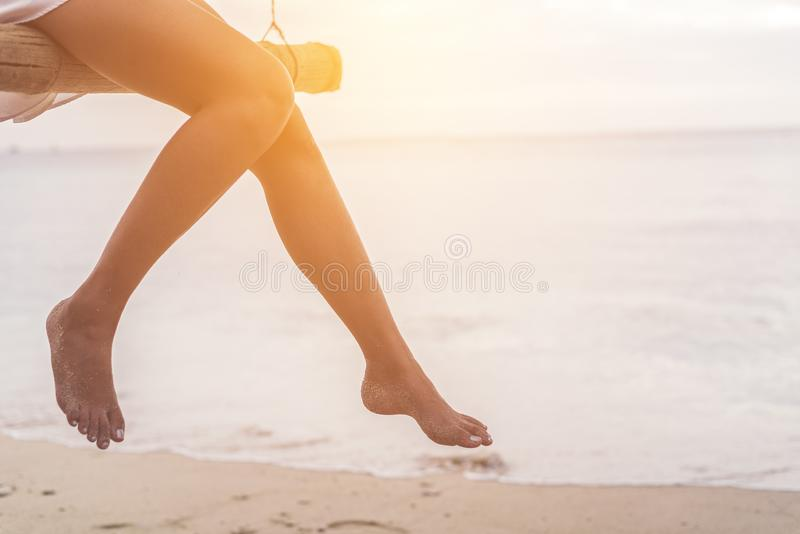 Woman legs at beach on wooden swing. Relax and Single woman concept. Happiness and lifestyle concept. Lonely and sadness concept. Beach and sea theme. Finding royalty free stock images