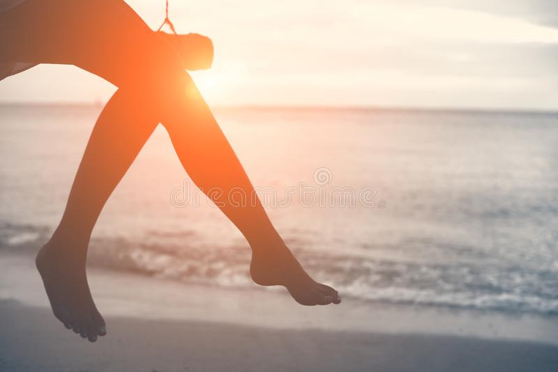 Woman legs at beach on wooden swing with sunset. Single woman co royalty free stock images