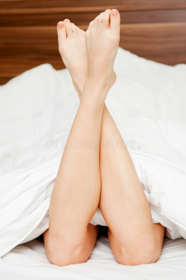 Woman legs in the bed royalty free stock photo