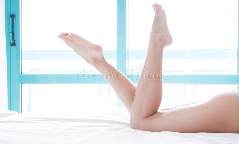 Woman legs on the bed in white bedclothes against a bright window background, beauty lifestyle concept.  stock photos
