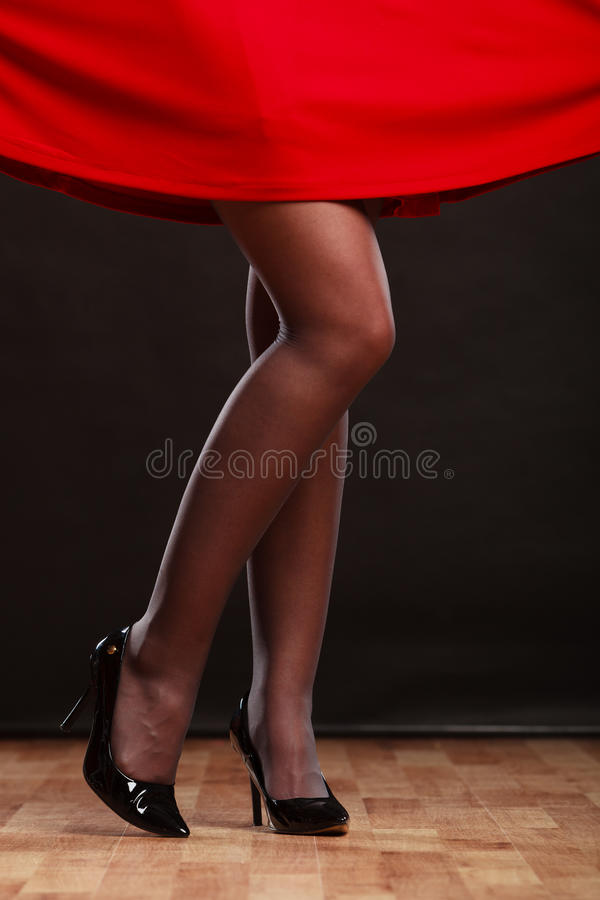 Woman legs in black high heels on party floor. New year celebration disco concept - woman in evening dress dancing in the club, part of body female legs in black royalty free stock photography