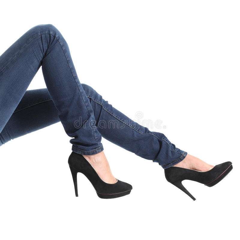 Woman legs with blue jeans and black platform heels. Close up of a woman legs with blue jeans and black platform heels isolated on a white background royalty free stock image