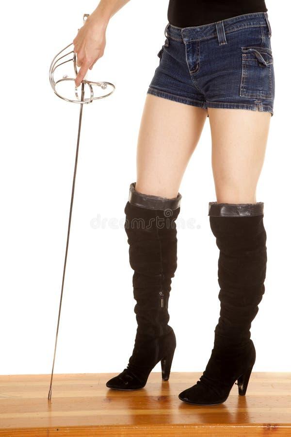 Woman legs boots sword stock photo