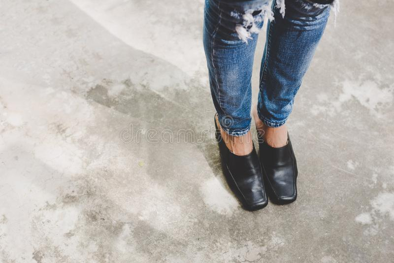 Woman legs in denim pants black stylish high heels shoes outdoo stock images