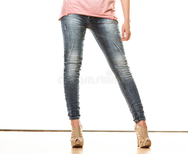 Woman legs in denim trousers high heels shoes. Fashion and people concept. Woman legs in denim trousers platform high heels shoes casual style isolated on white stock image