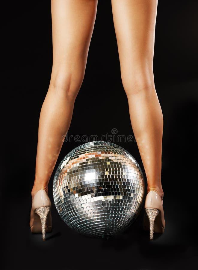 Woman legs and disco ball stock photo