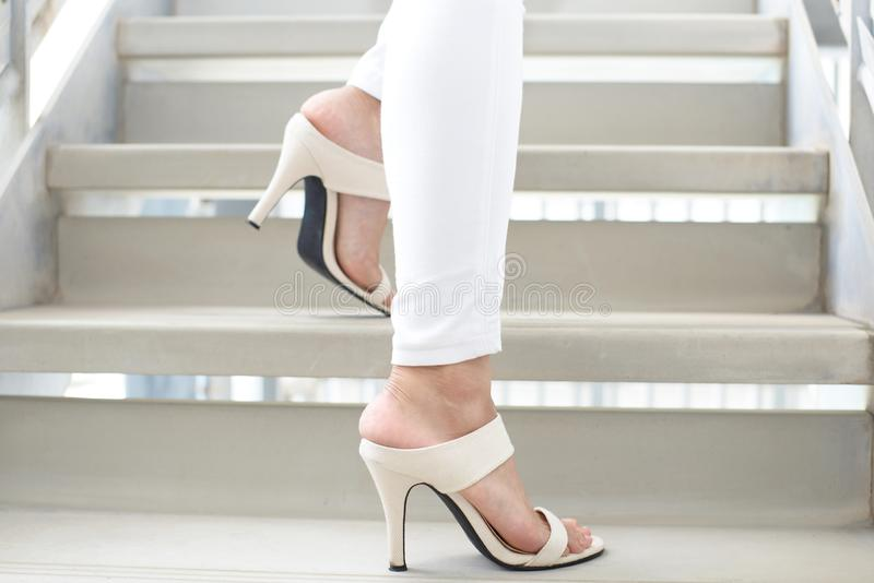 Woman legs in fashionable high heel sandals. Woman feet wearing white heel sandals stock images