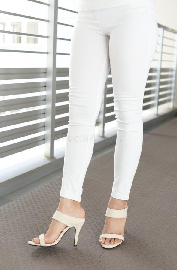 Woman legs in fashionable high heel sandals. Woman feet wearing white heel sandals stock photo