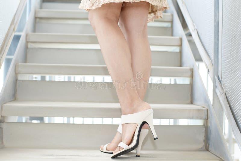 Woman legs in fashionable high heel sandals. Woman feet wearing white heel sandals royalty free stock photo
