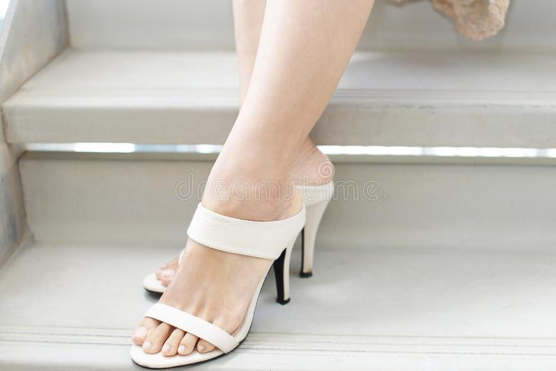 Woman legs in fashionable high heel sandals. Woman feet wearing white heel sandals stock photography