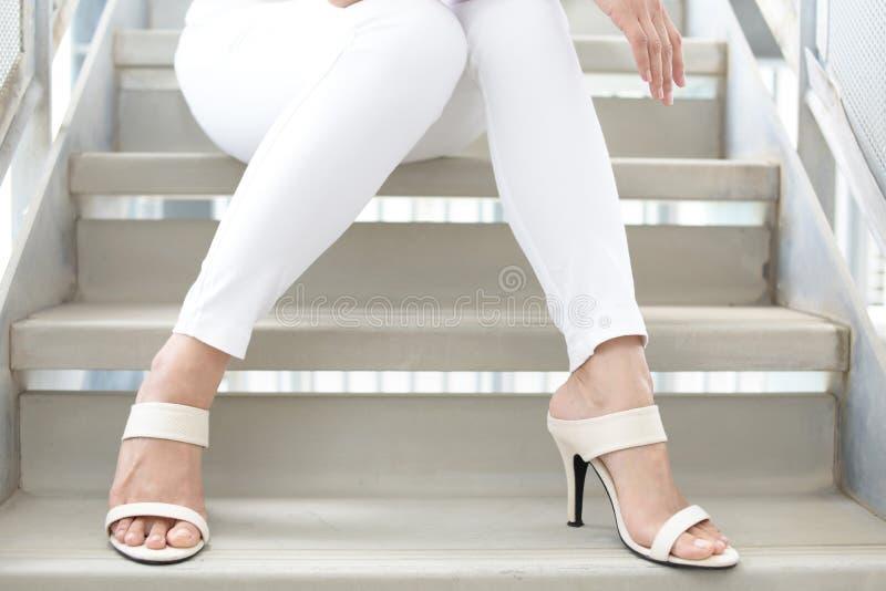 Woman legs in fashionable high heel sandals. Woman feet wearing white heel sandals stock image