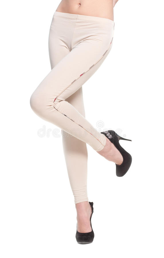 Woman legs in fawn leggins and black shoes. Close up of woman legs in fawn leggins and black shoes on white stock photo