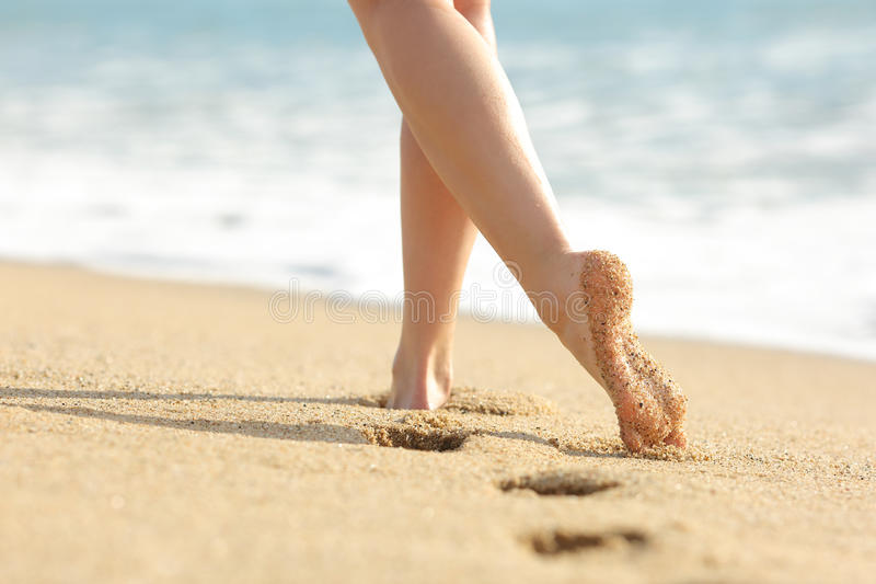 Woman legs and feet walking on the sand of the beach. With the sea water in the background stock photos