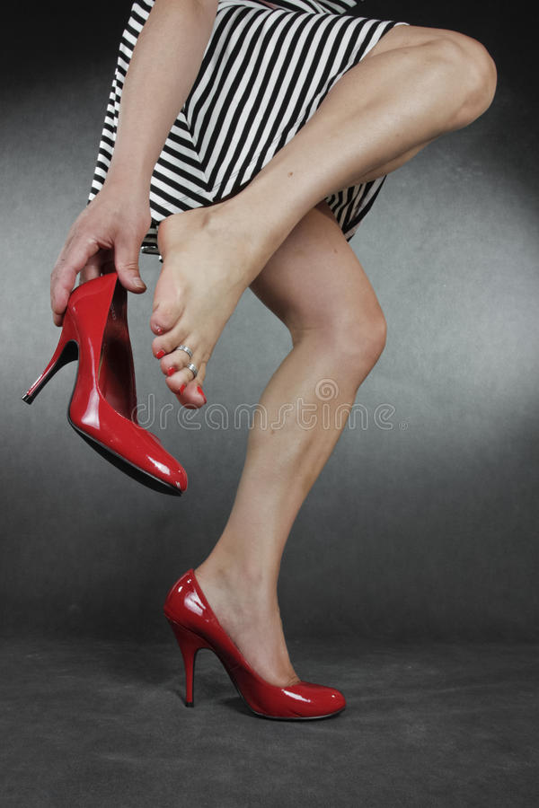 Woman legs and feet wearing dress putting on shoes over grey b. Ackground stock images