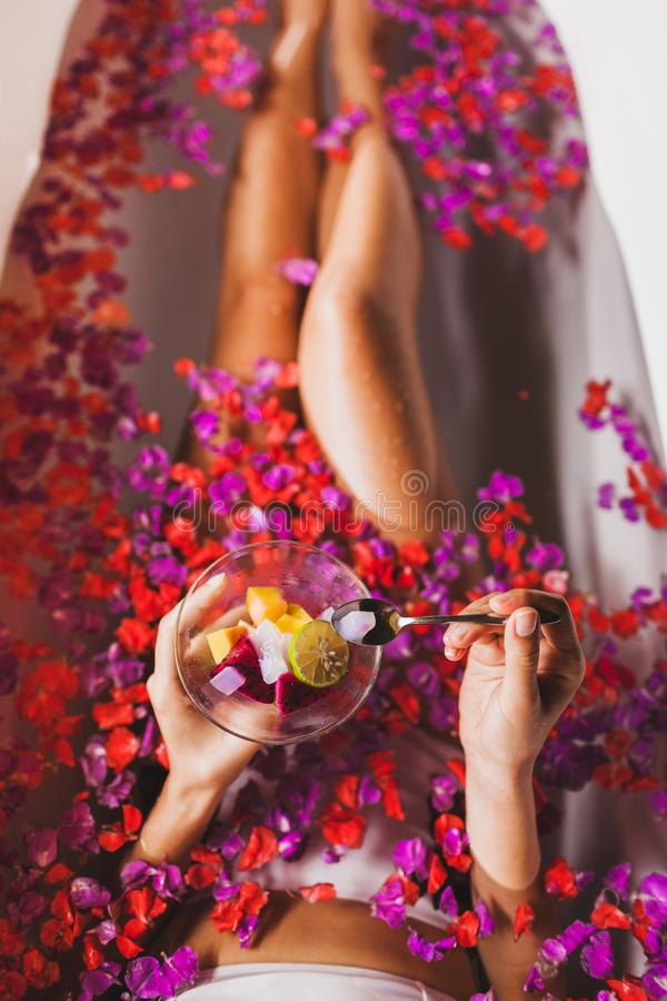 Woman legs in flower bath in spa, eat fresh fruits. Woman legs in flower bath in spa. Hands holding plate with fresh fruit salad, view from above royalty free stock image