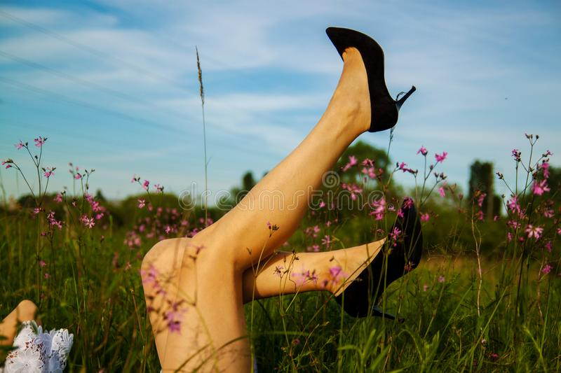 Woman legs in heels in the grass in summer. Relax and Single woman concept. Happiness and lifestyle concept. Healthy leg veins royalty free stock photo