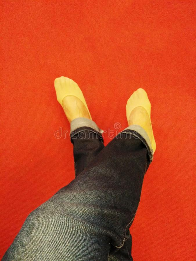 Woman legs in jeans, feet on red floor stock photos