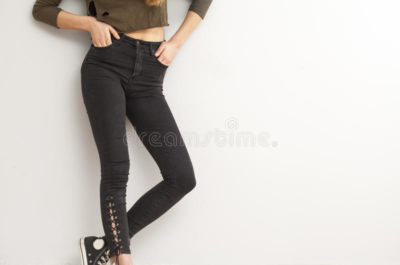 Woman legs in jeans on gray background stock images