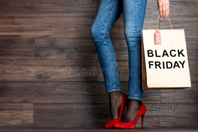 Woman legs in jeans and red high heels. Black Friday concept. Woman female adult girl legs in jeans and a new bought red high heels and shopping bag with text ` royalty free stock photo