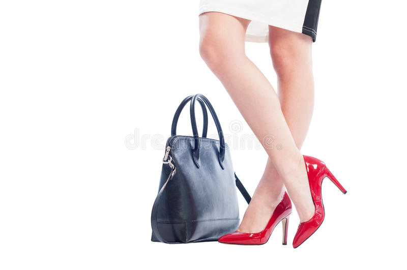 Woman legs, red shoes and black handbag or purse stock photo
