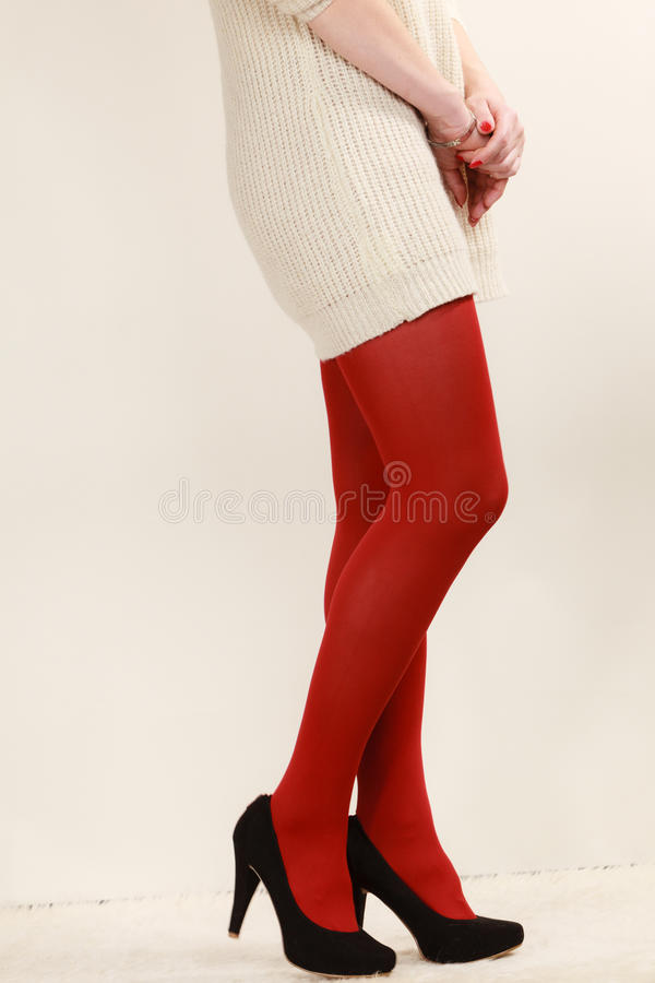 Woman legs in red vivid color pantyhose black high heels shoes stock photography