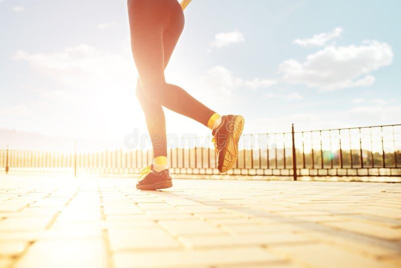 Female runner feet running at sunrise. Woman legs running in the rays of sun. Female runner feet running at sunrise closeup on legs. Girl fitness jog workout stock image