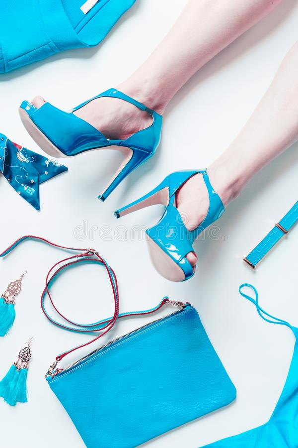 Woman legs in sexy turquoise bright pumps lie on white floor background with fashion outfit accessories: handbag, belt, churches,. Jacket,silk top. Top view stock photos