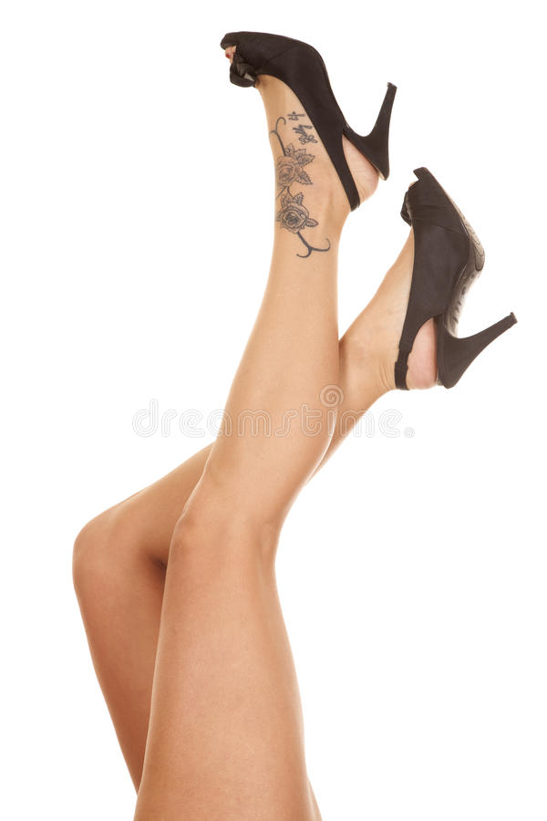 Woman legs tattoo on foot kicked up royalty free stock image