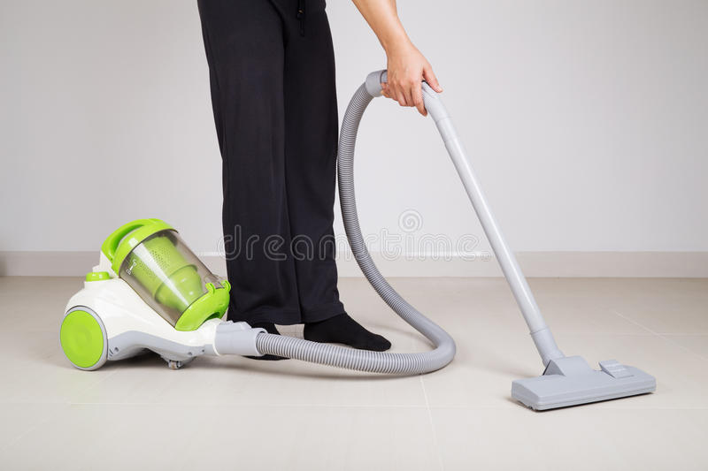 Woman legs with vacuum cleaner cleaning floor stock photography