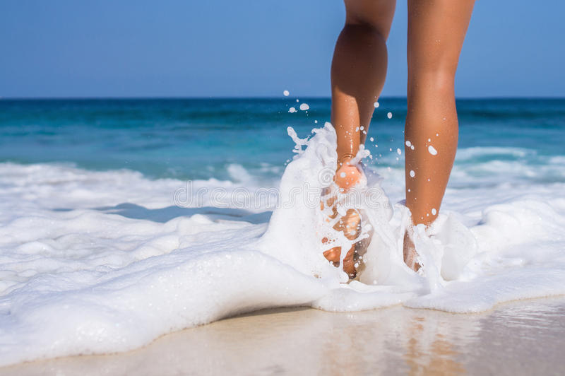Woman legs, walking on the beach. Blue sea and sky royalty free stock photo