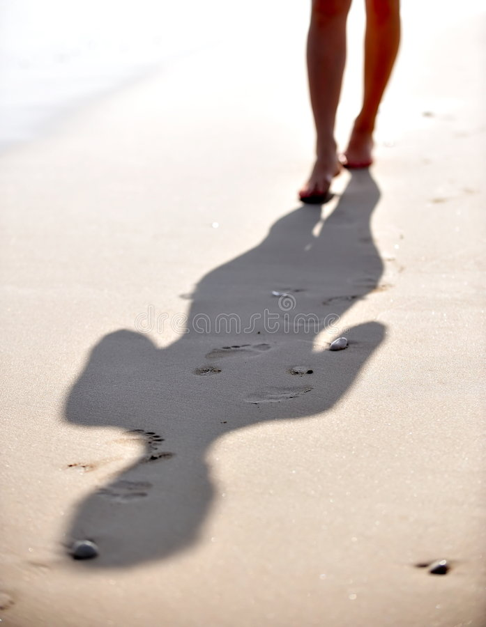 Woman legs walking on wet sand royalty free stock photos