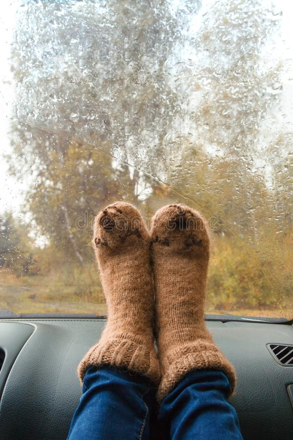 Woman legs in warm cute socks on car dashboard. Drinking warm tee on the way. Fall trip. Rain drops on windshield. Freedom travel. Concept. Autumn weekend stock image