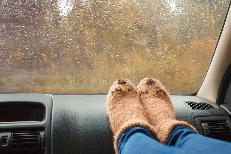 Woman legs in warm cute socks on car dashboard. Drinking warm tee on the way. Fall trip. Rain drops on windshield. Freedom travel. Concept. Autumn weekend stock images