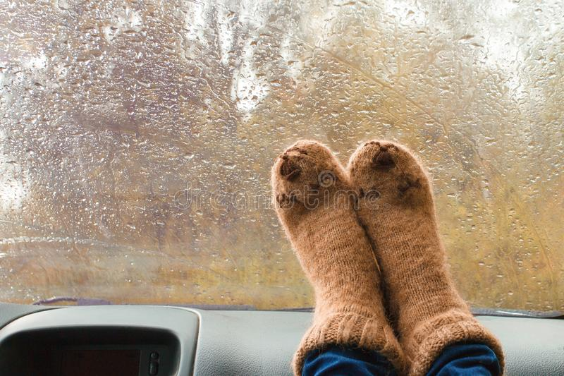 Woman legs in warm cute socks on car dashboard. Drinking warm tee on the way. Fall trip. Rain drops on windshield. Freedom travel. Concept. Autumn weekend stock photography