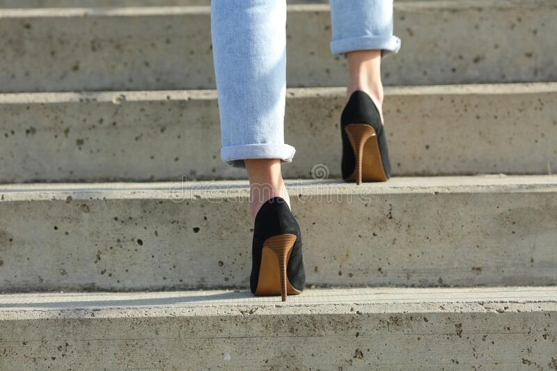 Woman legs wearing high heels walking up stairs royalty free stock image