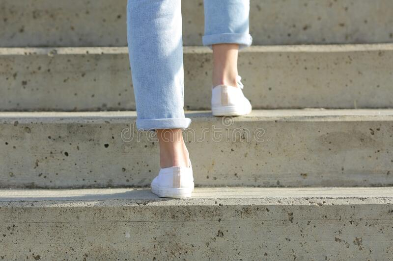 Woman legs wearing sneakers walking up stairs royalty free stock photography