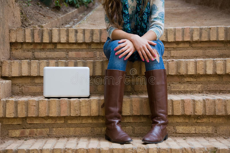 Woman legs with a white computer next stock images