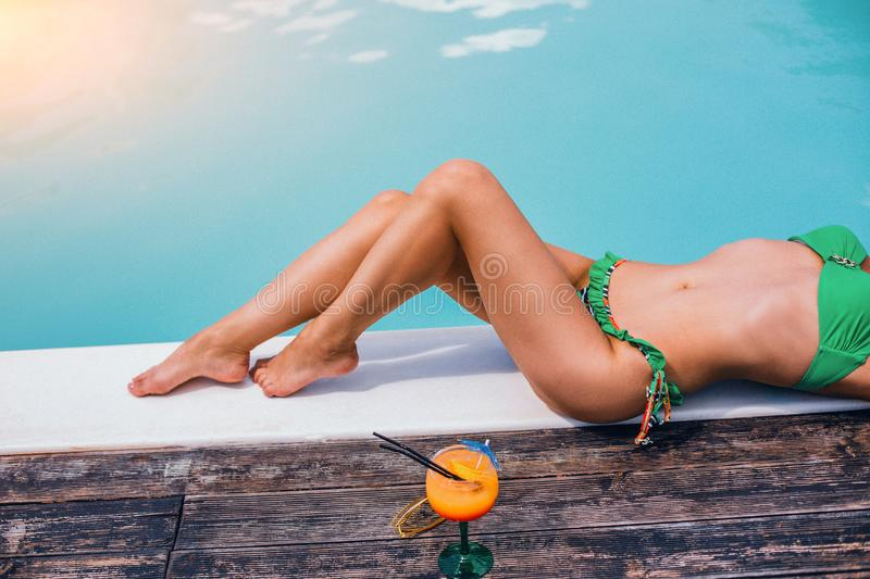 Woman Legs Who is Laying By The Swimming Pool. stock photos