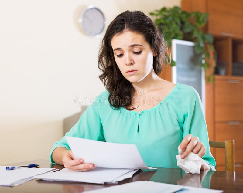 Woman with a letter in his hand. Woman crying and reading documents sitting at the table at home royalty free stock photo