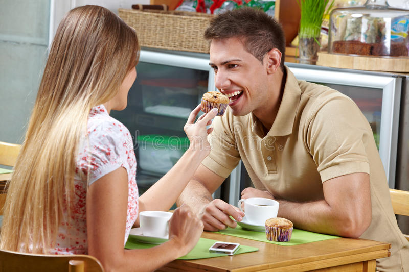 Woman letting man taste a muffin