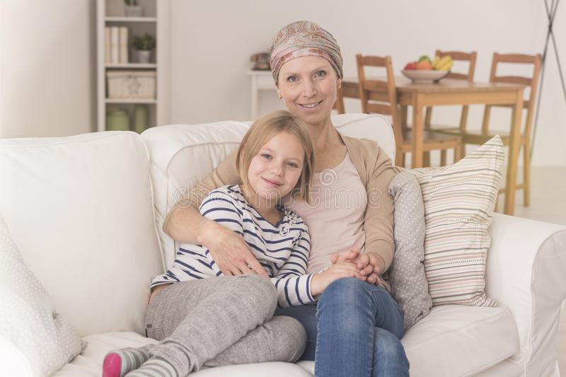 Woman with leukemia with daughter. Woman with leukemia wearing headscarf spending time with child daughter royalty free stock photography