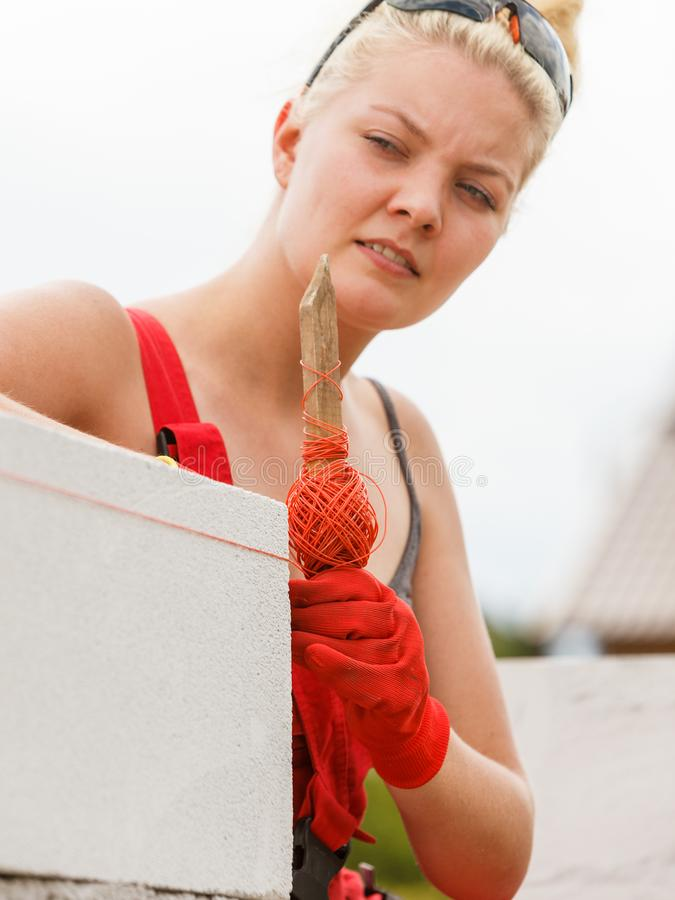 Woman leveling airbricks on construction site stock images