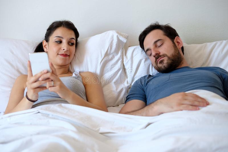 Woman liar having affair and chatting with other man while boyfriend is asleep royalty free stock photography