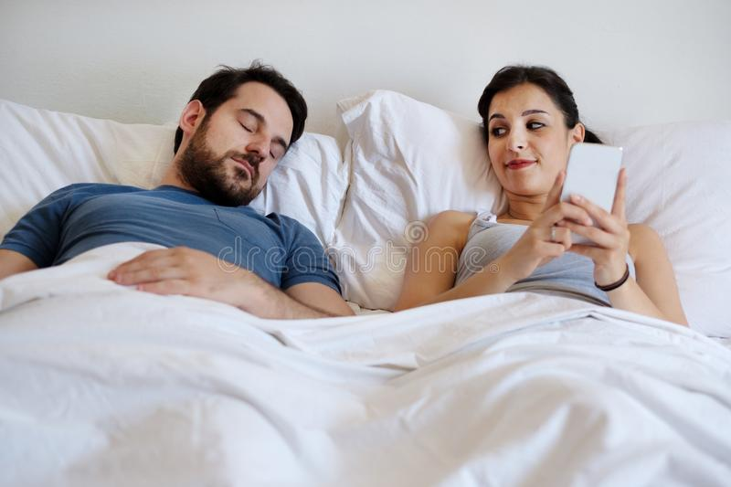 Cheating wife using mobile phone lying in bed next to his sleeping husband royalty free stock photos